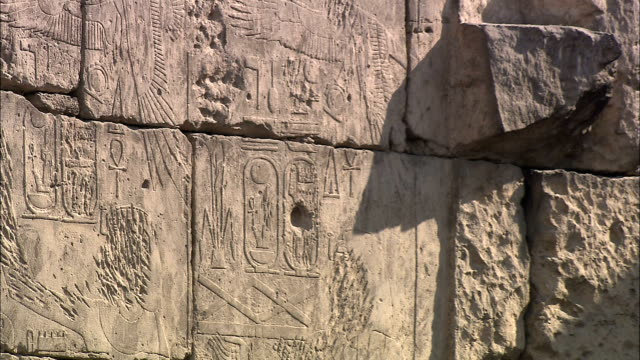 carvings decorate an ancient and weathered stone wall. - weathered stock videos & royalty-free footage