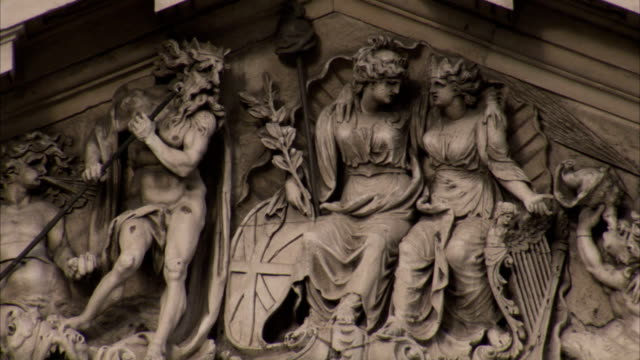 stockvideo's en b-roll-footage met carvings of men and women decorate a triangular accent on the four courts building. available in hd. - snijwerk
