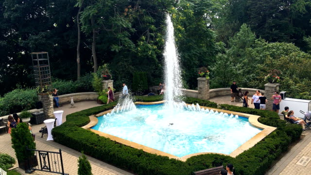 Casa Loma gardens fountain in summertime with people Casa Loma is a medieval castle and major tourist attraction