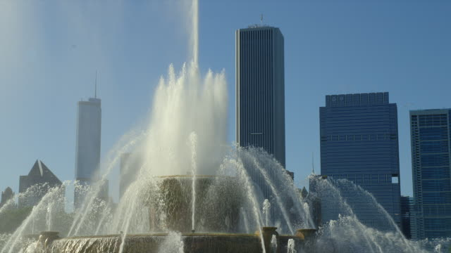 a cascade of fountains spray up in buckingham fountain in grant park in front of the chicago, illinois skyline. - buckingham fountain stock videos & royalty-free footage