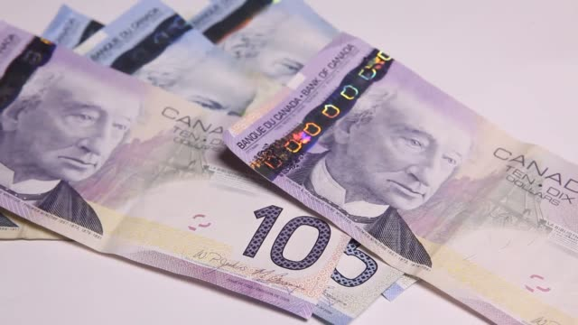 Cash and Coins falling into frame Canadian Dollar Canadian Currency on February 26 2013 in Toronto