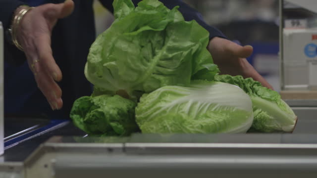 a cashier at a uk supermarket passes lettuce and packets of ready-prepared salad leaves through a till at a uk supermarket. - vegetable stock videos & royalty-free footage