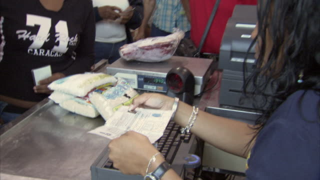 MS CU ZI Cashier checking women's ID card at check out at Mission Mercal store / Cabimas, Zulia, Venezuela