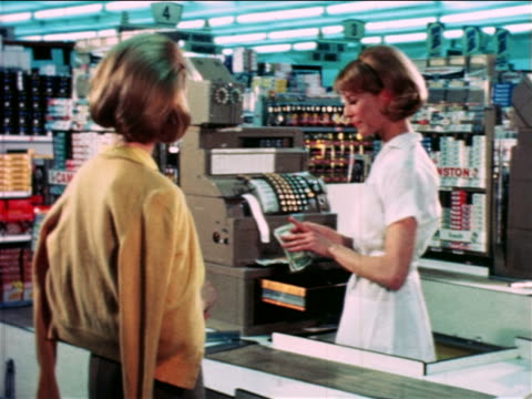 vídeos y material grabado en eventos de stock de 1965 cashier counting change for female customer in grocery store / educational - paying