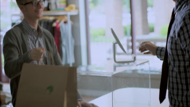 Cashier hands brown paper shopping bag to customer at checkout in modern clothing store
