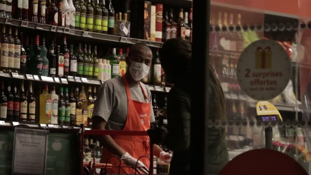cashier in a supermarket wears a sanitary mask to protect himself during the coronavirus epidemic crisis on march 20, 2020 in chambery, france. - cashier stock videos & royalty-free footage