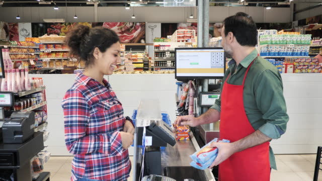 cashier in supermarket - female customer paying by contactless credit card - paying stock videos & royalty-free footage