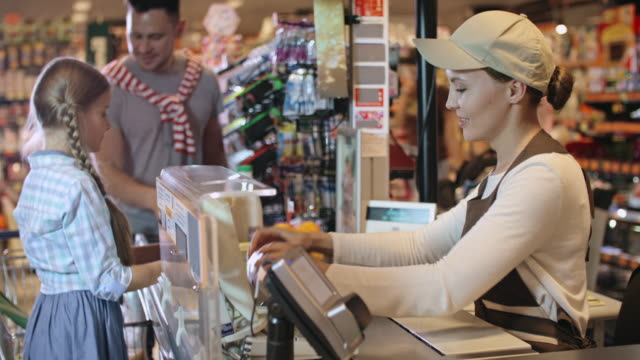 Cashier scanning groceries chosen by father and daughter