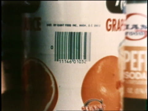 A cashier scans a bar code on a can of juice