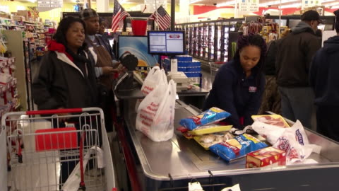 vídeos y material grabado en eventos de stock de cashier stands at register and bags groceries at supermarket in memphis, tennessee. zoom out on shopper paying for food supplies to prepare before... - bolsa de plástico