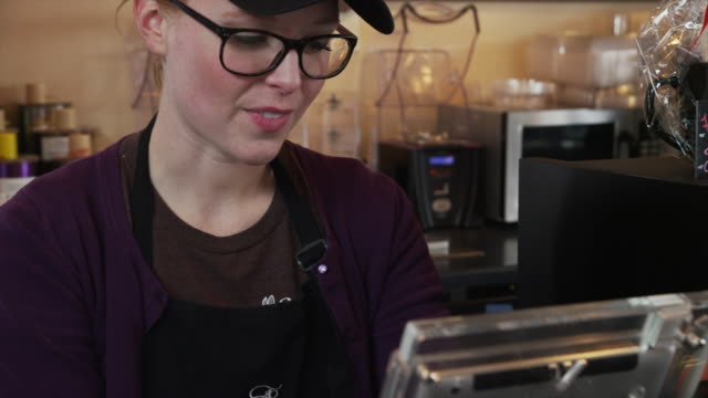 Cashier swiping customers credit card in cafe / Orem, Utah, United States,
