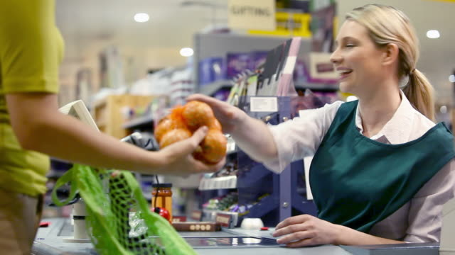 cashier talking to customer at supermarket checkout - tragetasche oder tragebeutel stock-videos und b-roll-filmmaterial