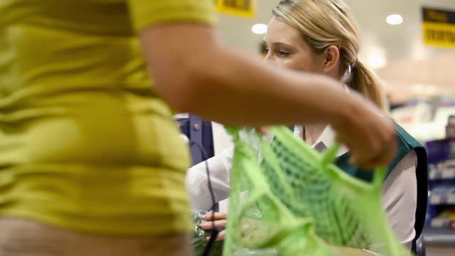 cashier talking to customer at supermarket checkout - weibliche person stock-videos und b-roll-filmmaterial