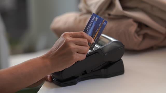 vidéos et rushes de caissier à l'aide d'un lecteur de carte de crédit - boutique