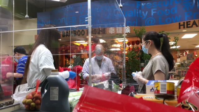 cashier wearing mask at a chinese grocery in atlanta, usa amid the 2020 global coronavirus pandemic - chinese culture stock videos & royalty-free footage