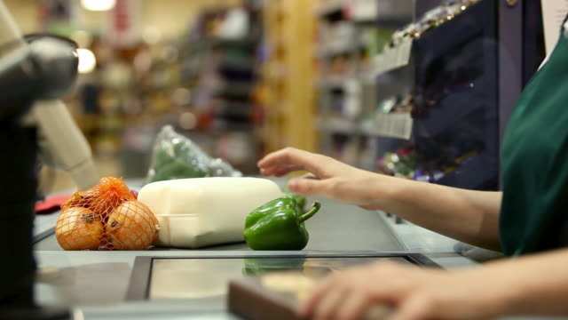 stockvideo's en b-roll-footage met cashier weighing and scanning items at supermarket checkout, close up - supermarkt