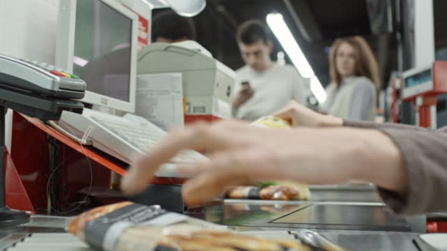 cashier working at checkout in supermarket - fare la fila video stock e b–roll