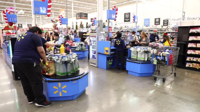 stockvideo's en b-roll-footage met cashiers ring up customers at registers inside a walmart stores inc location in burbank california us on thursday nov 16 2017 photographer patrick t... - wal mart