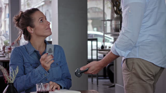 Cashless payment scene while day in a stylish coffee shop bar, woman in her 30s with brown hair wearing jeans shirt pays her drink with smart phone using wireless technology and Near Filed Communication, male waiter in beige chino and light blue shirt.