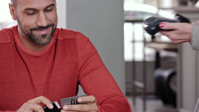 cashless payment while day - Latin man in his 30s wearing a reddish sweater, short dark hair and beard pays his bill with a credit debit card in a stylish café using wireless and near field technology, the waitress holds the wireless credit card reader