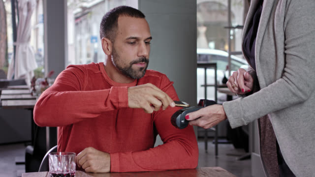 cashless payment while day - Latin man in his 30s wearing a reddish sweater with short dark hair and three-day beard pays his bill with a mobile phone in a stylish café using wireless and near field technology, the waitress holds the credit card reader
