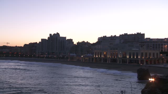 A casino and many buildings line the shore of Biarritz, France.