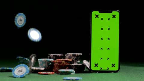 casino chip fällt in der nähe von smartphone mit green screen, gaming-token, online-casino-anwendung, chance zu gewinnen - poker stock-videos und b-roll-filmmaterial