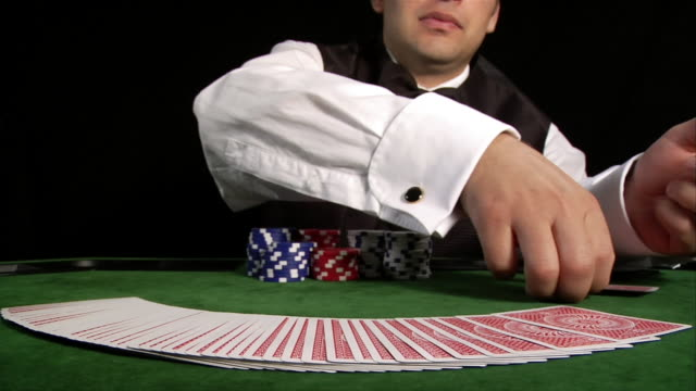 casino dealer fanning deck of cards across table, flipping cards face up and down, and unspreading deck - casino worker stock videos and b-roll footage