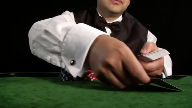 casino dealer laying out hand of cards on table - dealing cards stock videos and b-roll footage