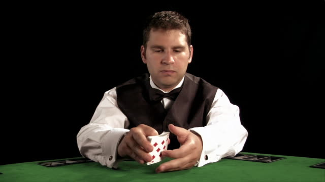 casino dealer shuffling deck of cards on table / dealing out cards - dealing cards stock videos and b-roll footage