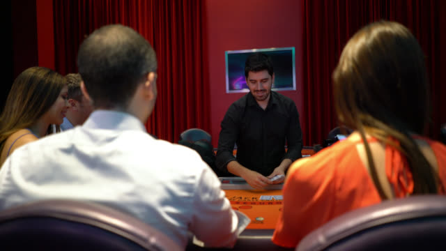 Casino worker dealing the cards at a poker table