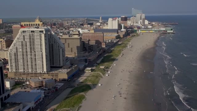 vídeos de stock, filmes e b-roll de casinos and resorts tower above the boardwalk at atlantic city. - atlantic city