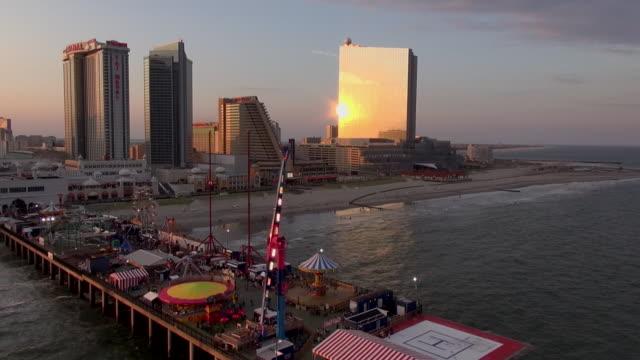 vídeos de stock, filmes e b-roll de casinos line the beach where a pier juts onto the ocean in atlantic city. - atlantic city
