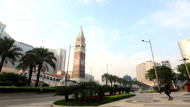 casinos unidentifiable people walking up sidewalk palm trees vehicles driving up down street venetian macao resorthotel skyscrapers clock tower w/... - cotai strip stock videos and b-roll footage