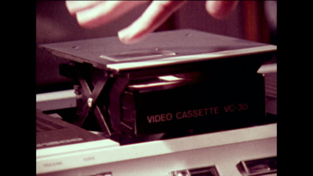 vídeos de stock e filmes b-roll de cassette being loaded into a vcr and played; 1973 - videocassete