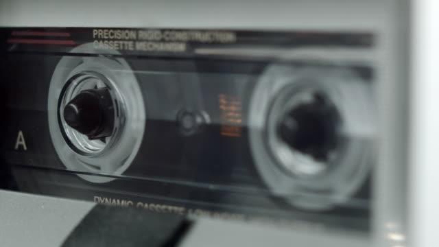 stockvideo's en b-roll-footage met cu cassette tape playing side view - cassettebandje