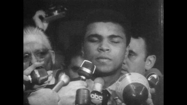 vidéos et rushes de cassius clay steps out of us customs house in houston to crowd of waiting press as he faces a possible 5year prison term for efusal to take the oath... - 1967