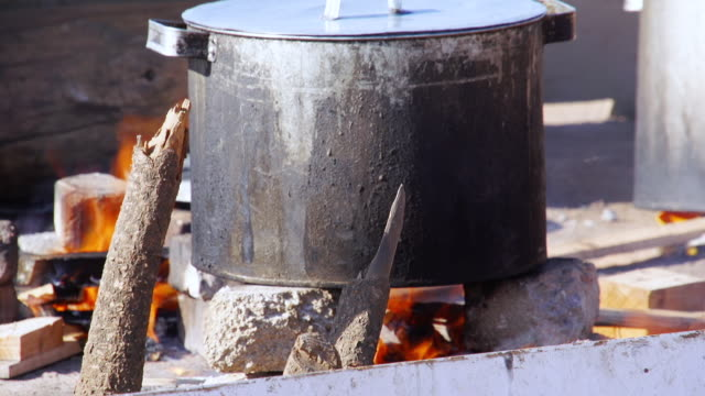 cu cast iron pot cooking on open fire / cosmo city, south africa - ハウテング州点の映像素材/bロール