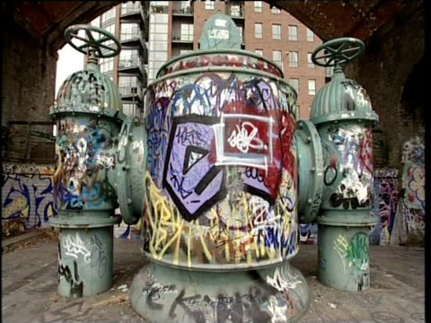 cast iron water pipes covered with graffiti paint under bridge - cast iron stock videos and b-roll footage