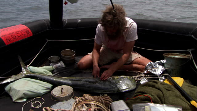 a castaway weakly eats raw fish as his raft drifts on the open sea. - überleben stock-videos und b-roll-filmmaterial