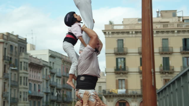 casteller kid climbing human pilar castle (one person per floor). teamwork from catalonia - danger stock videos & royalty-free footage