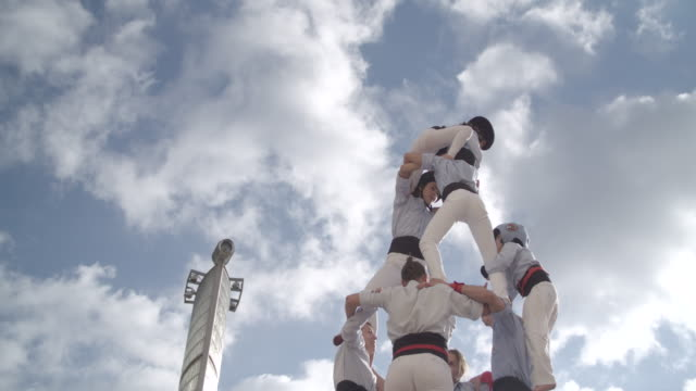 Casteller kid climbing to the top of human pyramid
