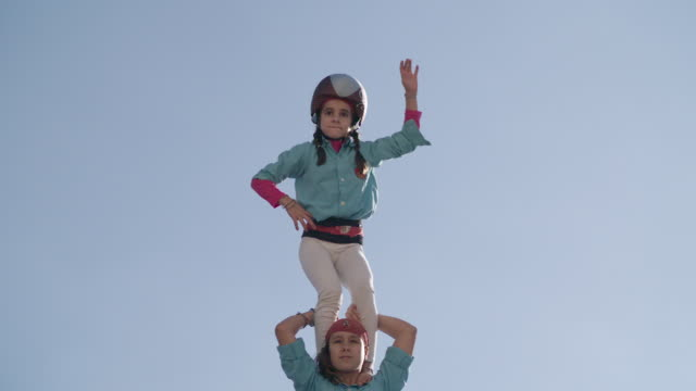 casteller kid climbing to the top of human pyramid - 肩に乗せる点の映像素材/bロール