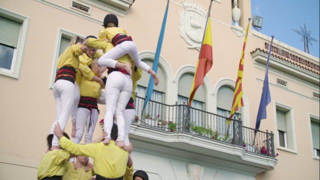 castellers children clmbing down human pyramid - human pyramid stock videos and b-roll footage