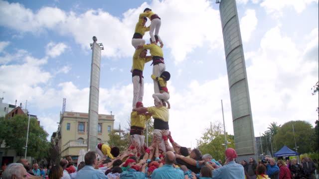 castellers climbing down human pyramid teamwork - human pyramid stock videos and b-roll footage