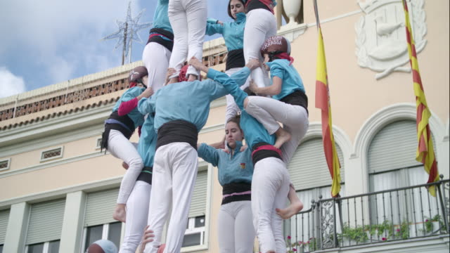 castellers climbing human pyramid teamwork from catalonia - gymnastics stock videos & royalty-free footage