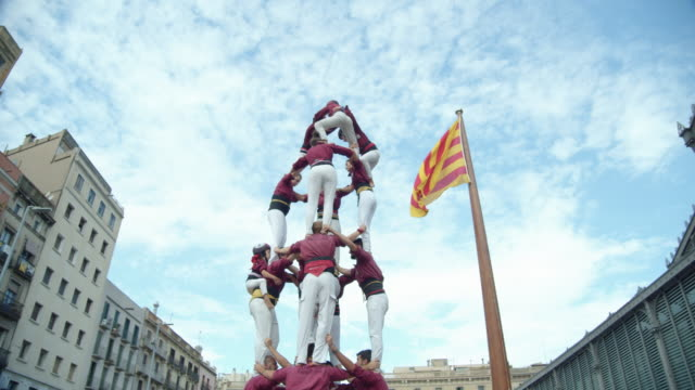 castellers disassembling a human castle. big catalonia flag on the background - dismantling stock videos & royalty-free footage