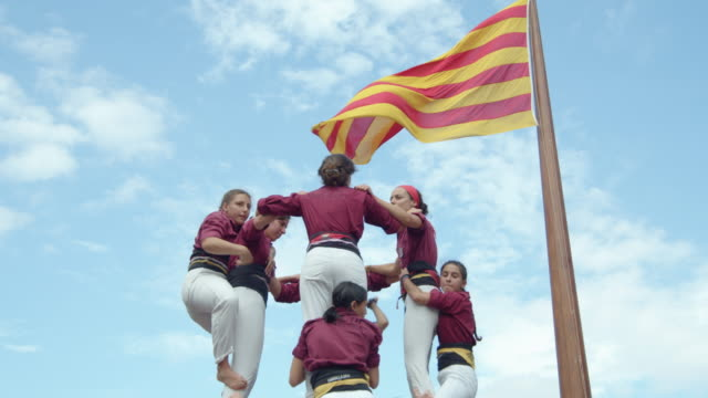 castellers disassembling a human pyramid. big catalonia flag on the background - dismantling stock videos & royalty-free footage