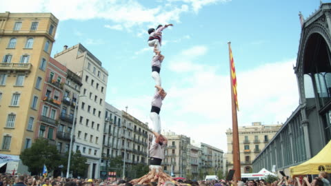 castellers finishing a successful human castle pilar (one person per floor). anxaneta (kid on the top) arriving to the castle peak. catalonia teamwork tradition - spanish culture stock videos & royalty-free footage