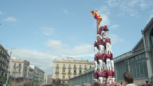 castellers human pyramid teamwork from catalonia. big catalan flag on the background - tradition stock videos & royalty-free footage